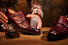 Man shining shoes with a rag. Stock Image