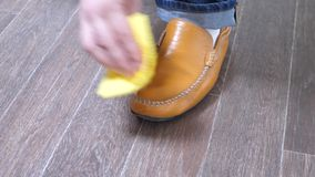 Man shining shoes with a rag. Man shining orange leather shoes with a yellow rag stock video