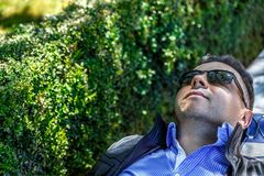 A man in a shirt and black glasses rests placidly on a bench. In a park royalty free stock photos
