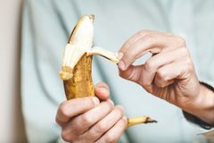Man in shirt clean banana. Male hand in a shirt holding a ripe banana and clean it stock photography
