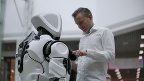 A man in a shirt communicates with a white robot asking questions and pressing the screen with his fingers. stock video footage