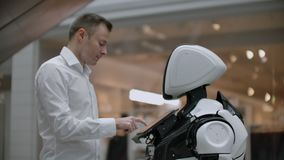 A man in a shirt communicates with a white robot asking questions and pressing the screen with his fingers. stock footage