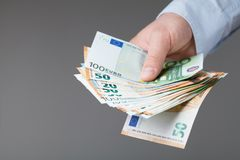 Man in shirt holding euro money in his hands. Banking, salary and donate concept. Man in shirt holding euro money in hands. Banking, salary and donate concept Stock Photos