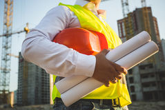 Man in shirt and jacket holding hardhat and blueprints Royalty Free Stock Photos