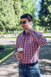 Man in shirt and jeans glasses, talking on the phone, smartphone, the concept of summer, businessman vacation. royalty free stock photo