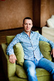 Man in shirt and jeans sitting Royalty Free Stock Image
