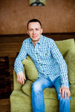 Man in shirt and jeans sitting Stock Photography