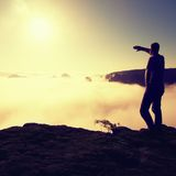 Man in shirt and jeans is standing on the peak of sandstone empire  and watching over the misty and foggy morning valley to Sun. B Stock Image