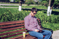 Man in  shirt and jeans  sunglasses, video looks on the tablet corresponds to the social networks, in the summer  the be Royalty Free Stock Photography