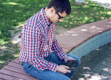Man in  shirt and jeans  sunglasses, video looks on the tablet corresponds to the social networks, in the summer  the be Royalty Free Stock Images