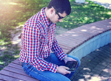 Man in  shirt and jeans  sunglasses, video looks on the tablet corresponds to the social networks, in the summer  the Stock Image