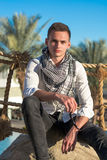 Man in a shirt and in a keffiyeh at the palm trees Royalty Free Stock Images