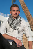 Man in a shirt and in a keffiyeh sits at the palm tree Stock Image