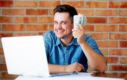Man in shirt with laptop computer and money. Young man in shirt with laptop computer and money brick wall on background stock photo