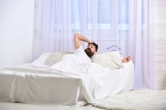 Man in shirt laying on bed awake, white curtain on background. Guy on shocked face waking up in morning. Macho with. Beard and mustache overslept waking up call Stock Image