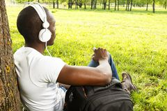 Man shirt listens music in a park Stock Photo