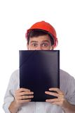 Man in a shirt orange construction helmet covers Stock Photo
