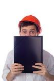 Man in a shirt orange construction helmet covers Stock Photo