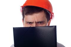 Man in a shirt orange construction helmet covers Royalty Free Stock Photo