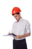 Man in a shirt orange construction helmet writes Royalty Free Stock Images