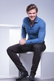 Man in shirt and pants is sitting and smiles Stock Photos