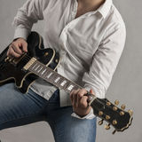 Man in shirt playing black electric guitar Stock Images