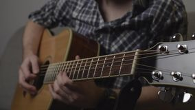 Man in shirt playing solo on acoustic guitar with pick slow motion full hd footage stock video footage