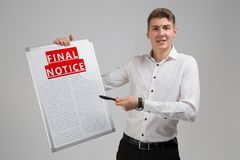 Young man holding final notice isolated on light background stock image