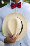 Man in shirt, red bow-tie holding white wicker hat Royalty Free Stock Photos