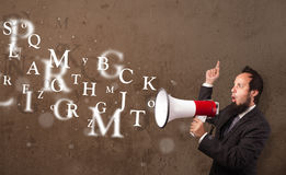 Man in shirt shouting into megaphone and text come out Stock Images