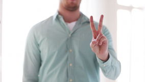 Man in shirt showing sign of victory by hand Royalty Free Stock Image