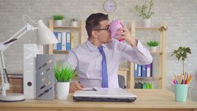Man in a shirt sitting at a laptop in the office with a piggy bank. In his hands stock video footage
