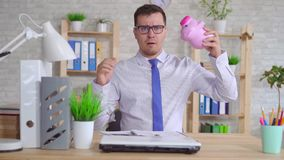 Man in a shirt sitting at a laptop in the office with a piggy Bank slow mo. Young man in shirt and glasses office worker shakes piggy Bank slow mo stock video footage