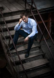 Man in shirt sitting on stairs Royalty Free Stock Photography