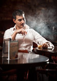 Man in shirt sitting at the table and smoking Royalty Free Stock Images