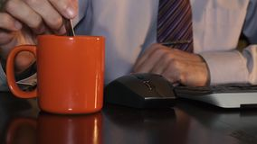 A man in a shirt stirs coffee while sitting in office stock footage