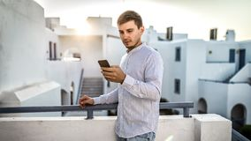 Guy businessman young man looks into the phone, dials number. White summer location outdoor  sunset greece. Guy businessman young man looks into the phone, dials royalty free stock images