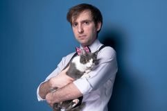 Man in shirt, suspender and pink bow tie looking at camera and holding adorable grey cat. Handsome man in shirt, suspender and pink bow tie looking at camera and royalty free stock image