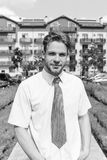 Man in shirt with tie or businessman with smiling face with building on background. Young man in yard of apartment. Man in shirt with tie or businessman with stock photos