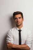 Man with shirt and tie leaning against a wall with crossed arms Stock Photography