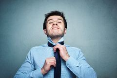 Man in shirt ties a tie with emotion on a gray background royalty free stock image