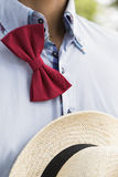 Man in shirt with untied bow-tie and wicker hat Stock Image