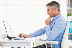 Man in shirt using laptop and thinking Royalty Free Stock Photos