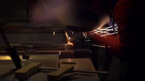 Man in a shirt shirt and wearing a protective mask conducts welding work. Sparks are flying stock video