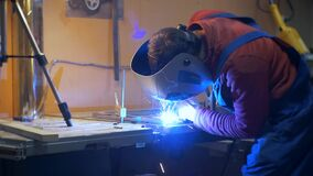 Man in a shirt shirt and wearing a protective mask conducts welding work. Sparks are flying stock video footage