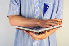 Man in shirt writing in his notebook Royalty Free Stock Images