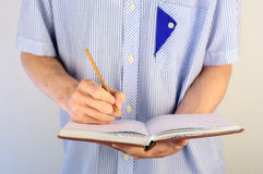 Man in shirt writing in his notebook Stock Image