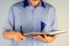 Man in shirt writing in his notebook Royalty Free Stock Image