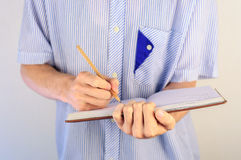 Man in shirt writing in his notebook Stock Photo
