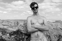 Man Shirtless Casual Beach Black White. Young man shirtless shades posing cool casual black and white portrait holidays beach ocean Royalty Free Stock Image